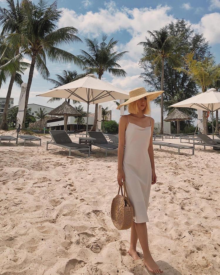 Chiếc nón cói cùng túi mây là cách giúp Quỳnh Anh Shyn không bị nhạt nhòa với chiếc váy hai dây đơn giản.