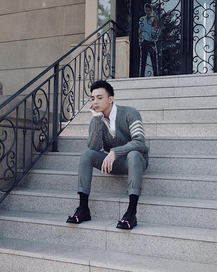 """Trên sân khấu """"quậy"""" tưng bừng là thế, mà sao trong bức ảnh này, Soobin Hoàng Sơn lại """"dịu dàng"""" đến bất ngờ. Anh chàng lựa chọn đôi giày đính nơ để làm nổi bật set đồ xám trung tính đi kèm biểu cảm tay nhẹ nhàng, nữ tính."""