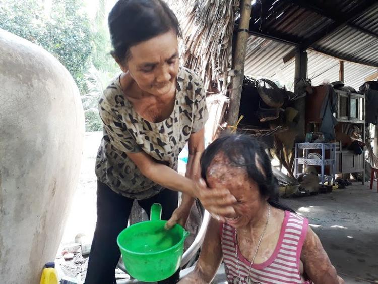 Bé N. tỏ ra hạnh phúc khi được bà nội rửa mặt. (Ảnh: Thanh Lâm).