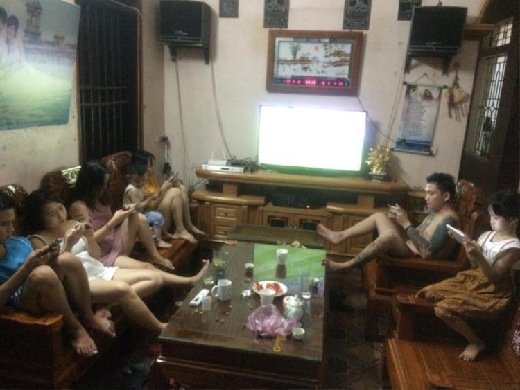 Trong bức ảnh, từ người lớn đến trẻ em, nam thanh, nữ tú đều dán mắt vào màn hình điện thoại trong khi màn hình tivi đang phát World Cup