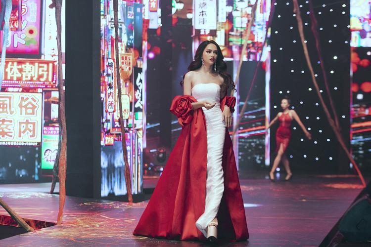 Hoa hậu Chuyển giới Quốc tế Hương Giang tiếp tục đốt mắt người nhìn bằng màn vũ đạo gợi cảm. Người đẹp diện thiết kế váy trắng kết hợp với chiếc áo choàng đỏ nổi bật phía ngoài. Mang giày cao gần 20cm nhưng người đẹp vẫn catwalk một cách uyển chuyển và tự tin.