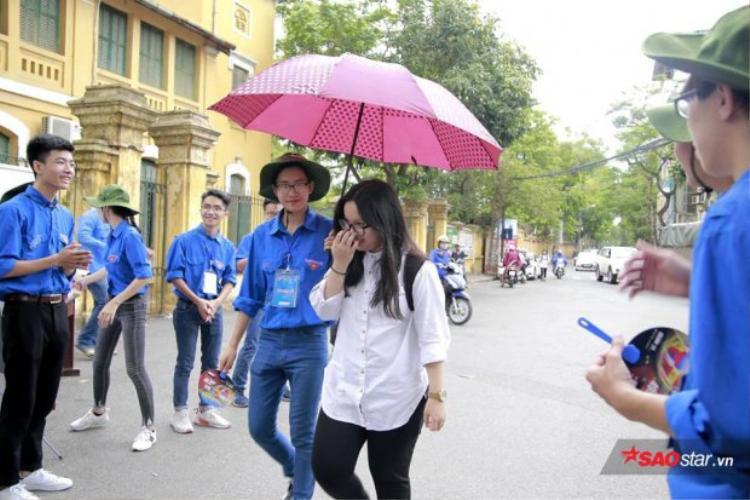 Hình ảnh thanh niên tình nguyện che ô cho thí sinh khi thời tiết Hà Nội bất chợt đổ mưa trong đầu giờ thi môn Toán chiều nay.