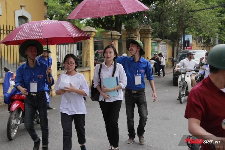 Các tình nguyện viên ở điểm thi THPT Trần Phú che ô cho sĩ tử.