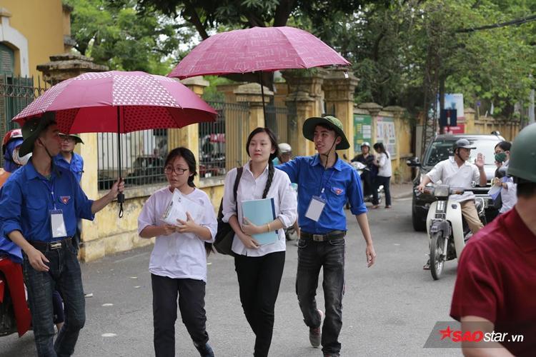 Các bạn nhường hầu hết phần ô che mưa cho sĩ tử tránh ướt.