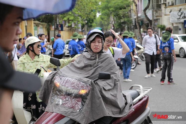Nhiều bậc phụ huynh phải mặc áo mưa dù trận mưa không lớn lắm.