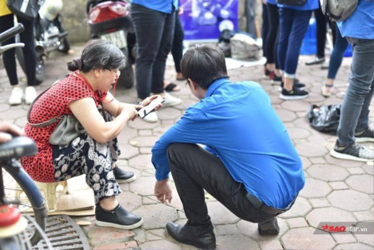 Một tình nguyện viên đang hướng dẫn cách sử dụng thiết bị điện tử cho phụ huynh lớn tuổi.