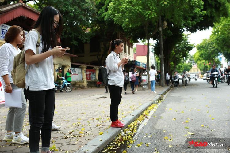 Tại điểm thi THPT Trần Phú, nhiều sĩ tử đứng ngoài cổng trường xem đáp án qua mạng.