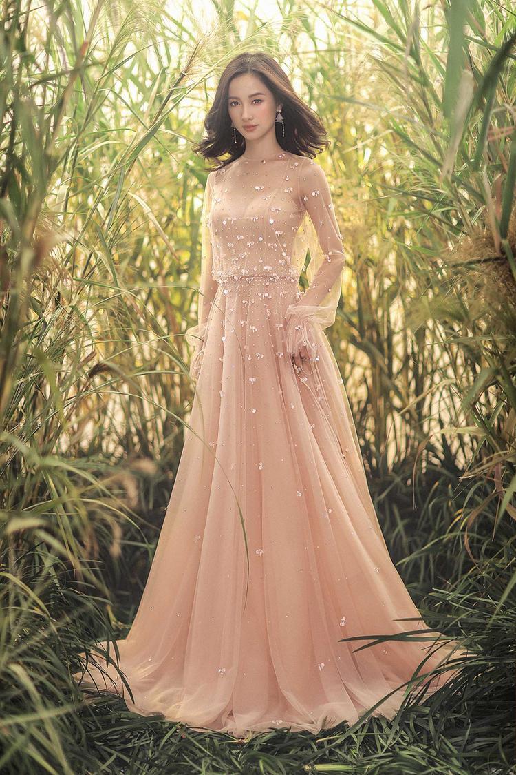 Chiếc đầm dạ hội với tay bồng nữ tính sẽ là thiết kế gây chú ý hơn cả, chất liệu lưới trong làm thanh thoát phần tay áo đồng thời đính kết sequin thủ công tỉ mỉ.