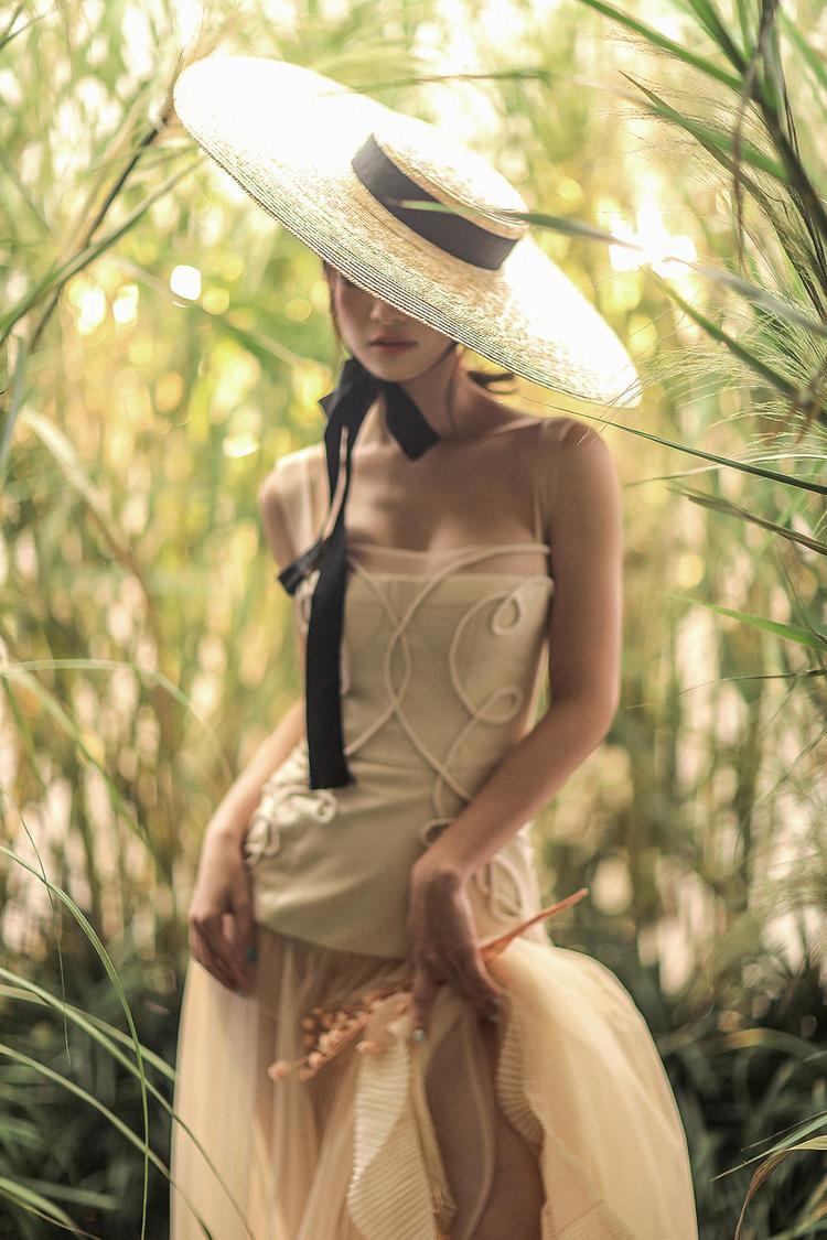 """Lấy bối cảnh cánh đồng cỏ lau đầy mộng mơ, bộ ảnh mới của Jun Vũ dễ dàng """"đốn tim"""" giới mộ điệu. Người đẹp đội nón rộng vành, che nửa khuôn mặt, tạo vẻ bí ẩn."""