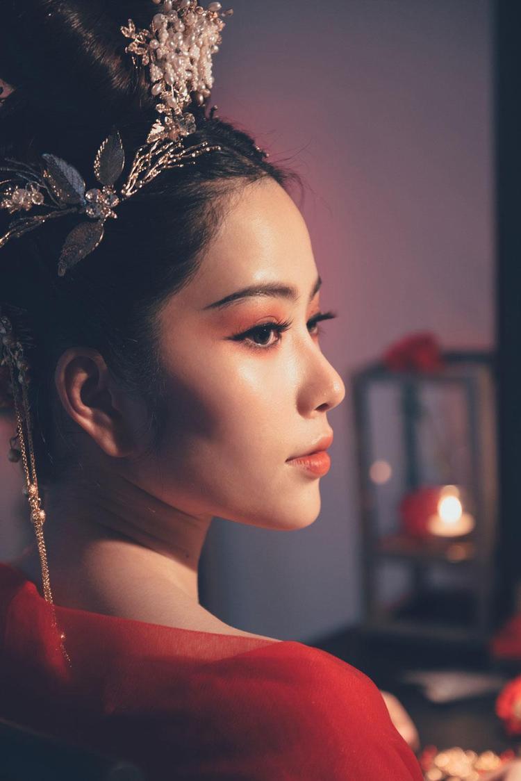 Ngay cả cách trang điểm môi đỏ hồng, khối mắt sâu cùng việc sử dụng phụ kiện cũng rất phù hợp, đặc tả được hình ảnh của một nữ hoàng mang mác.