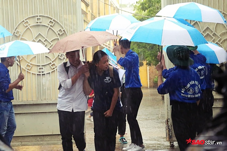 Các bạn thí sinh được tình nguyện viên che ô cho tới khi tìm được người nhà đến đón.