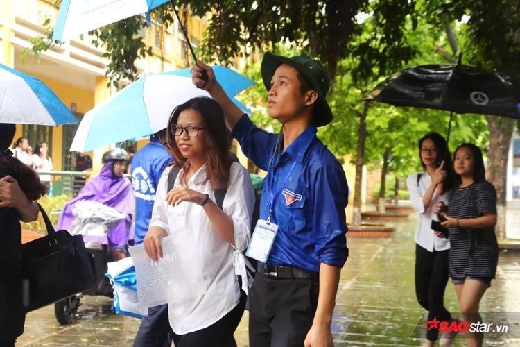 Mưa gió, sinh viên tình nguyện sẵn sàng nhường ô cho sĩ tử.