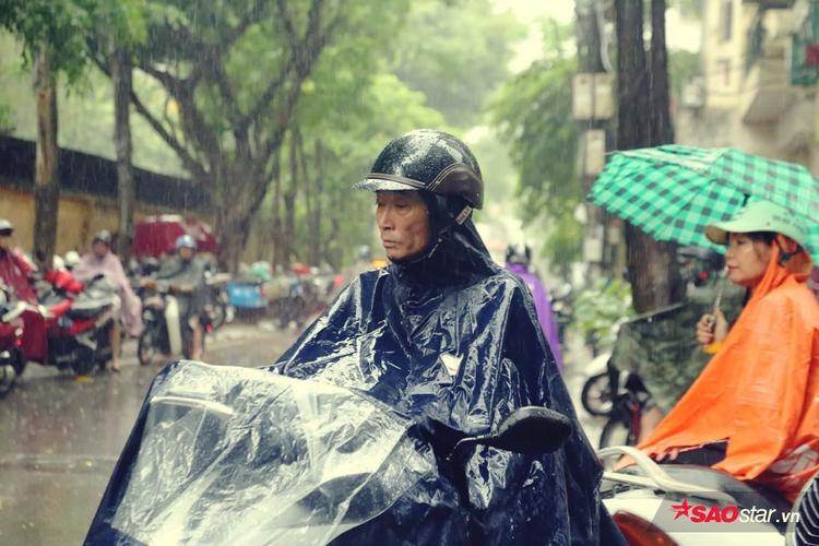 Bất chấp mưa lớn, phụ huynh đứng chờ con ở cồng trường.