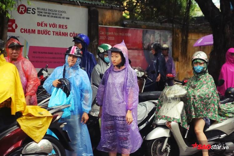 Các bạn thí sinh được người nhà mang áo mưa đến.