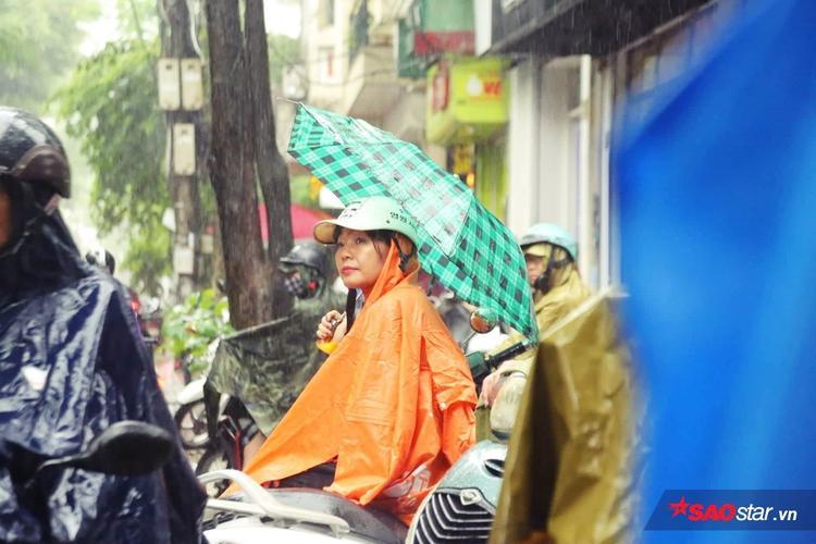 Phụ huynh cầm ô, mặc áo mưa đứng chờ.