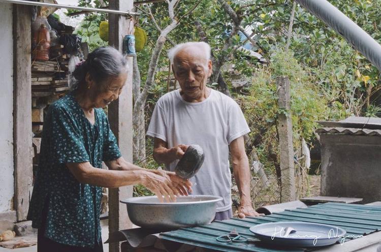 Ông múc nước cho bà rửa tay sau khi ra vườn về.