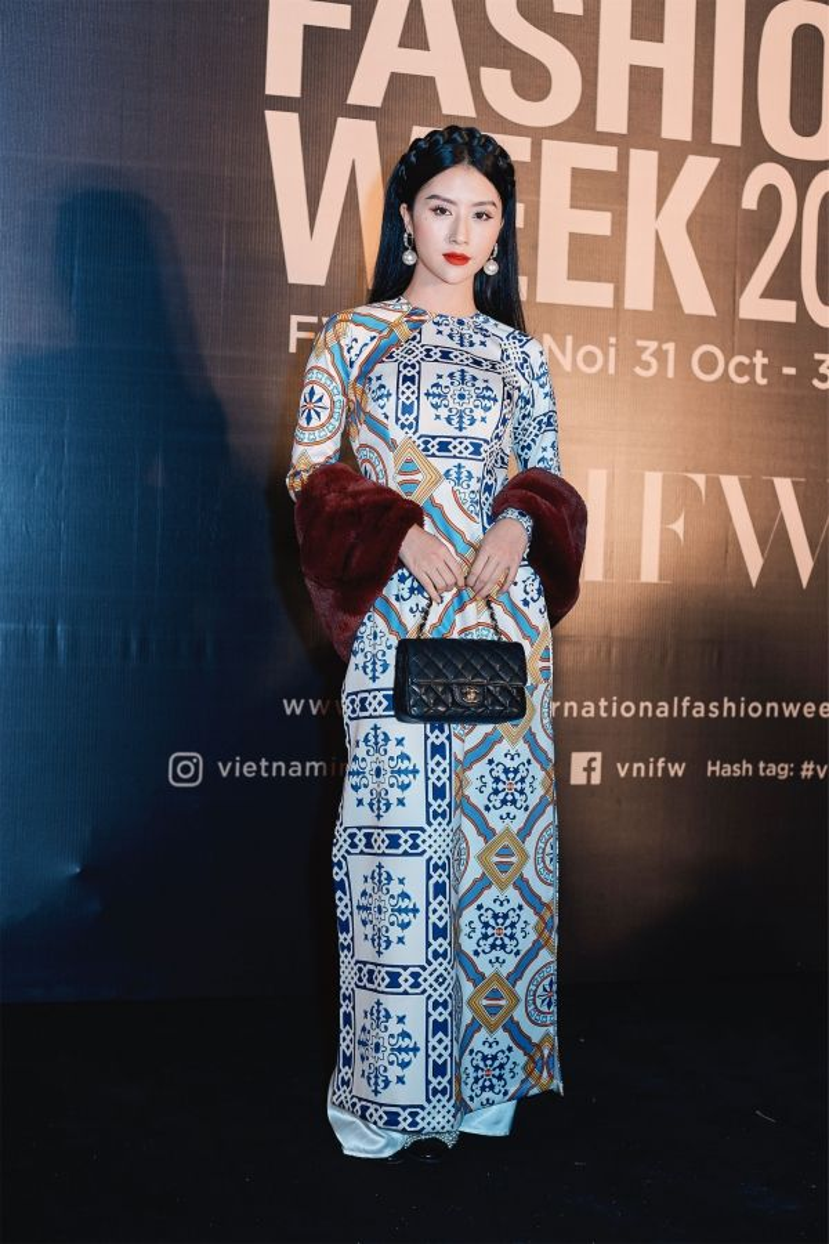 Áo dài họa tiết gạch bông được Quỳnh Anh chinh phục dễ dàng. Cô nàng đã khiến tà áo truyền thống thêm thú vị, phá cách bằng việc kết hợp với khăn choàng lông đỏ đô và túi Chanel cổ điển.