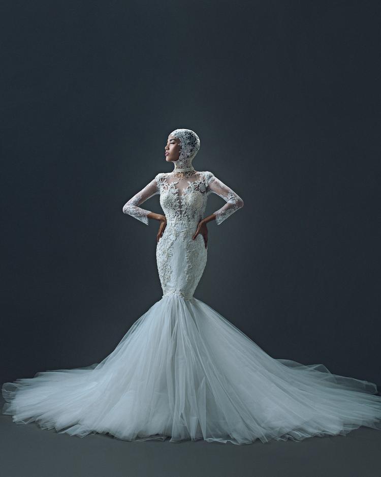 Các mẫu váy có kiểu dáng cổ điển cũng được cách tân về độ dài hay điểm xuyết thêm phụ kiện mũ đội đầu bằng vải voan cầu kỳ và tỉ mỉ, làm nên vẻ cuốn hút đầy phá cách cho cô dâu Lan Khuê.