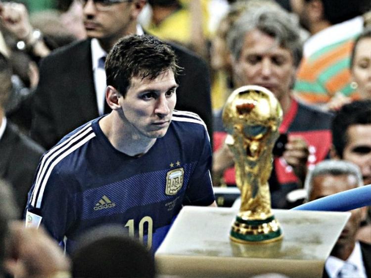 Messi nhìn Cúp vàng thế giới sau thất bại trước Đức. Ảnh: Reuters