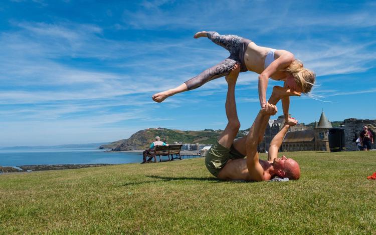 Cặp đôi luyện tập yoga trên ngọn đồi gần lâu đài Aberystwyth. Ảnh: Keith Morris