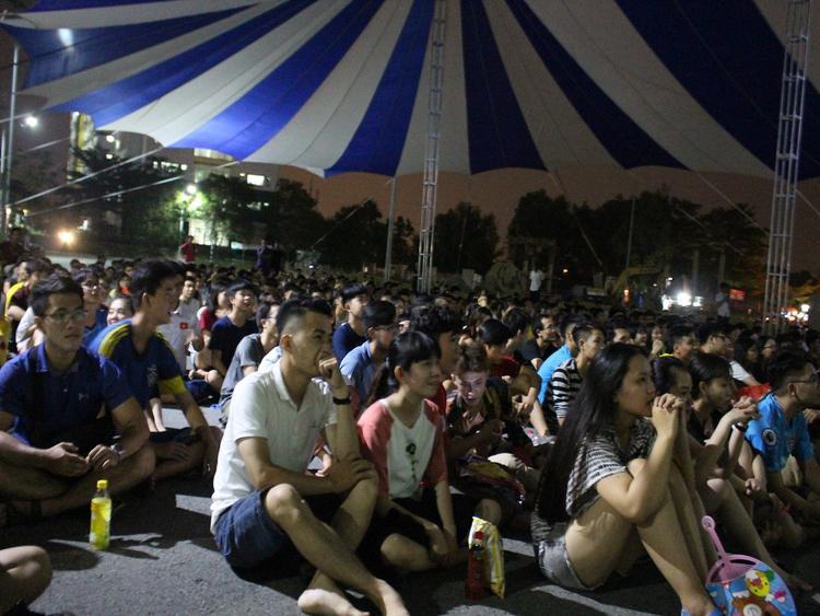Không ngại việc phải ngồi bệt xuống đất, các bạn sinh viên vẫn vui vẻ theo dõi trận đấu cùng nhau