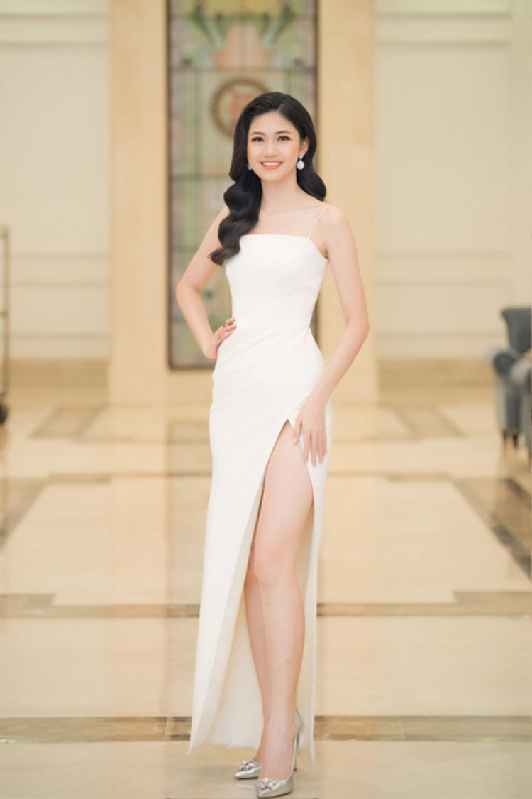 Á hậu Thanh Tú tinh khôi trong chiếc váy trắng đơn giản nhưng được cắt may một cách khéo léo. Chỉ cần kiểu tóc xoăn nhẹ nhàng và một đôi hoa tai là đã đủ giúp người đẹp ghi điểm.