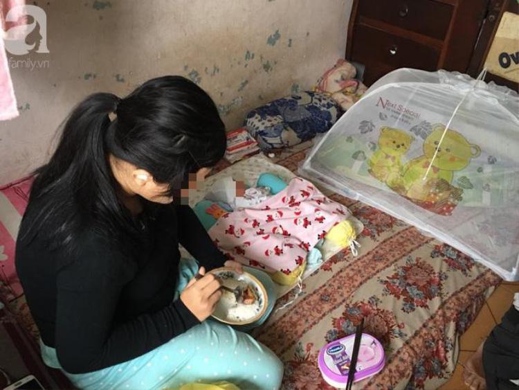 Bé Trang vừa ăn cơm vừa chăm sóc con trai nhỏ.