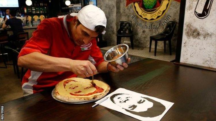 Anh Valery Maksimchik đang tỉ mẩn tạo hình cầu thủ lên bánh pizza. Ảnh: Reuters