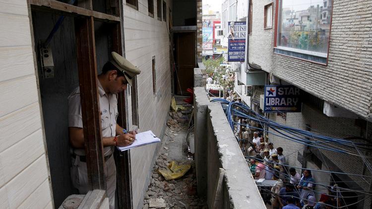 Cảnh sát khám nghiệm bên trong căn nhà - nơi 11 người trong một gia đình tử vong đồng thời. Ảnh: Reuters