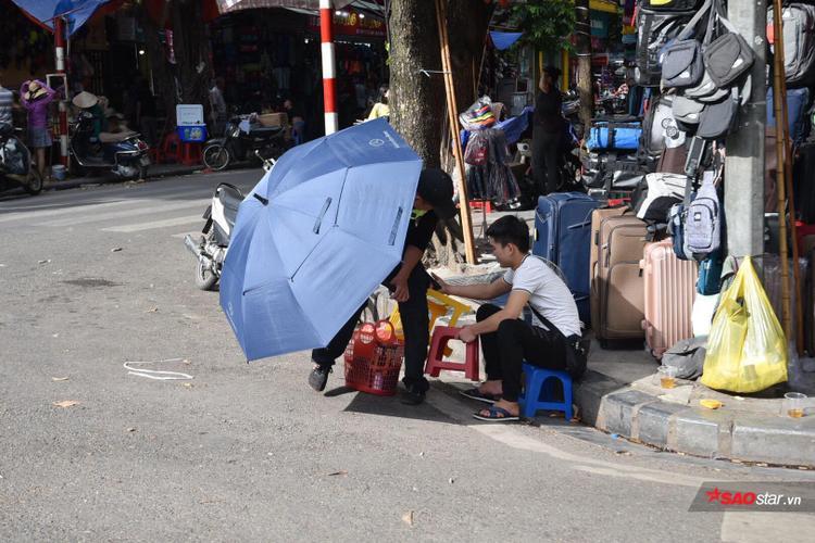 Để đối mặt với khó khăn của thiên nhiên, nhiều người nghĩ cách chống nắng nóng đơn sơ bằng những chiếc ô.