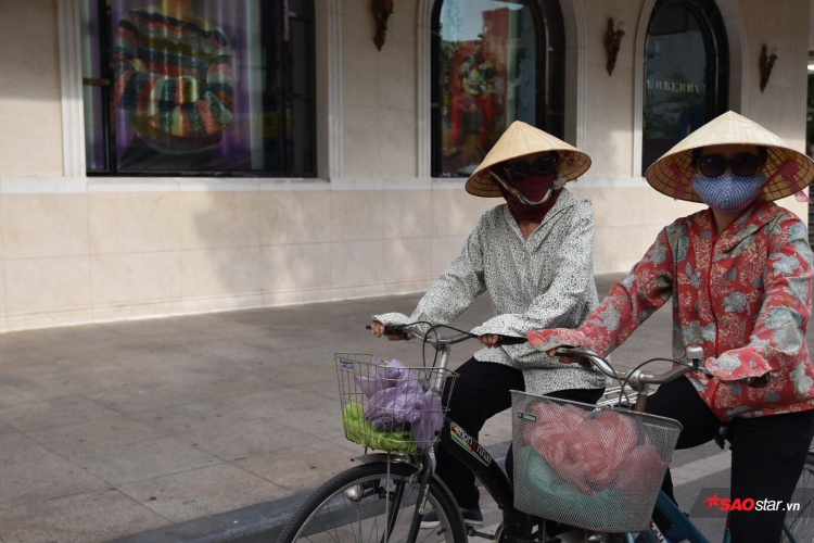 Hai người phụ nữ bưng bít kín mít đạp từng vòng xe nặng nhọc mang theo gánh nặng mưu sinh bất kể nhiệt độ ngoài trời ở Hà Nội lên đến gần 50 độ.