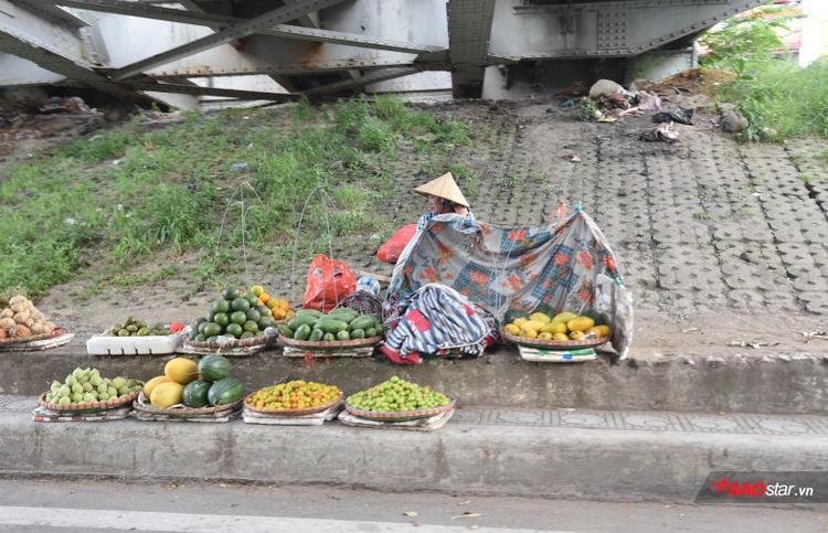 """Trong khi đó, một người bán hoa quả ở khu vực chợ Long Biên đã """"ngụy trang"""" bằng những tấm bạt để mong sao bán hết hàng."""