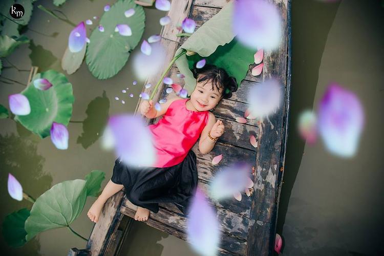 Hình ảnh đáng yêu của Mì Tôm nghịch ngợm bên nước và những cánh sen khiến các mẹ muốn sinh ngay 1 cô con gái và còn không ngớt lời khen bởi nhiều góc chụp tươi mát khác.