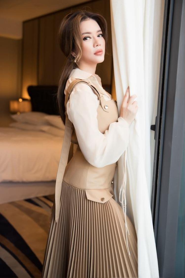 Cô lựa chọn kiểu váy yếm tông màu pastel kết hợp với sơ mi voan mỏng bên trong tạo cảm giác nhẹ nhàng nhưng không kém phần thanh lịch. Điểm nhấn của bộ trang phục nằm ở phần chân váy với những chi tiết xếp ly được thực hiện kỳ công.