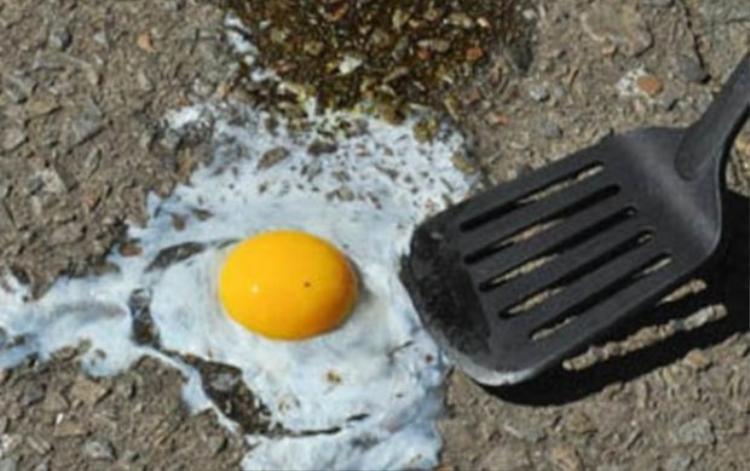 """Tại Ealing, Tây London vào ngày 30/6, nhiệt độ cao 32 độ C khiến trứng cũng bị chiên chín ngay trên lòng đường. Anh chàng Mark Kehoe chế biến """"bữa sáng"""" là món trứng ốp la ngay trên mặt đường trong những ngày nắng nóng ở Anh."""