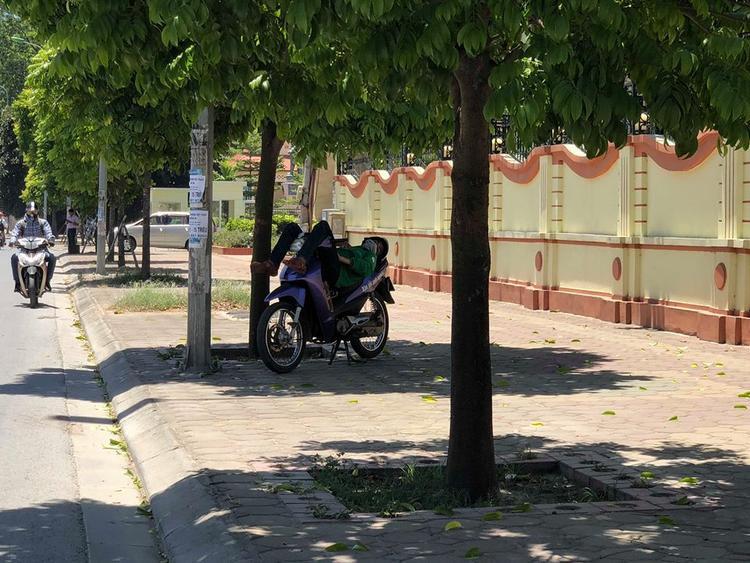 Một bạn trẻ chạy Grab tranh thủ nghỉ ngơi dưới một bóng râm ven đường trong tiết trời nắng nóng lên đến hơn 40 độ.