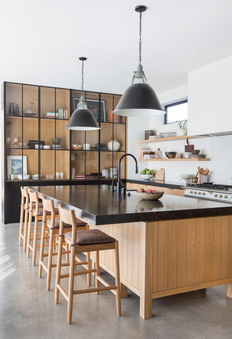 Bạn cũng có thể chọn mặt bàn đá đen cùng những chiếc đèn trang trí màu tối cho căn bếp của mình.