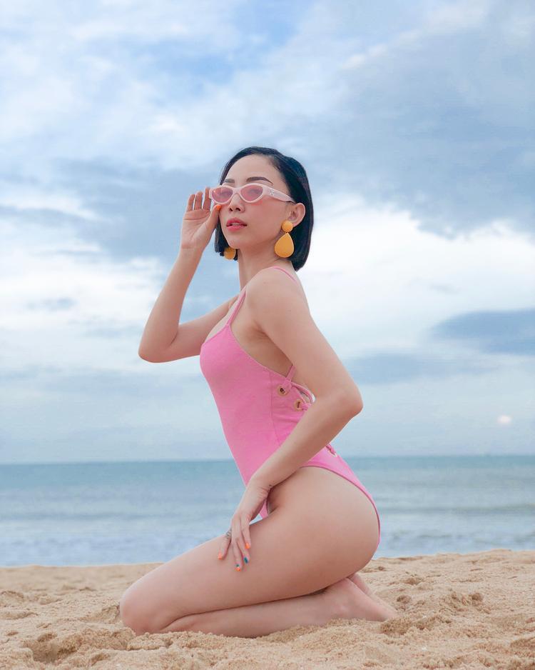 """Vóc dáng nuột nà của Tóc Tiên được tôn lên hết cỡ với áo tắm một mảnh gam màu hot pink. Giọng ca """"Ngày mai"""" còn khéo léo mix cùng hoa tai vàng theo xu hướng color block."""