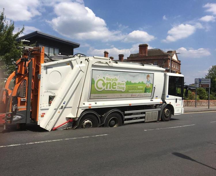 Hai bánh sau của xe chở rác bị lún trong nhựa đường.