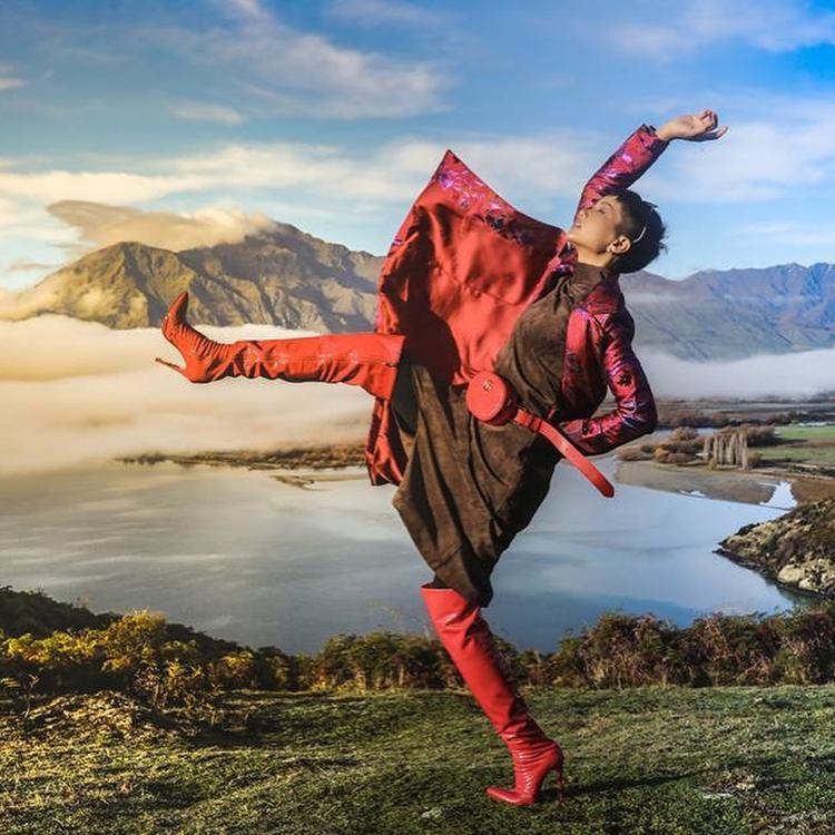 Cách tạo dáng đầy phiêu lãng và cá tính giúp hoa hậu nổi bật giữa thiên nhiên hoang dã, nhấn nhá cho sét đồ người đẹp chọn một đôi boots đỏ cao quá gối và 1 túi thắt eo đồng màu đến từ thương hiệu Gucci.