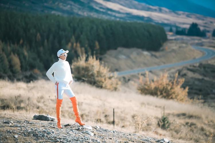 Trẻ trung và rạng rỡ với nguyên cây trắng từ quần áo cho tới phụ kiện mũ và mắt kính. Nhấn nhá bằng đôi boots cao màu cam nổi bật.