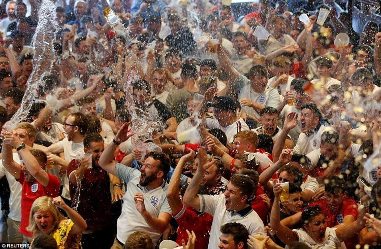 Đám đông tắm mát dưới mưa bia và nước ngọt. Ảnh: Reuters