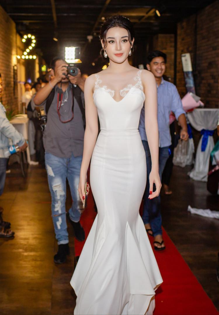 Bộ váy đuôi cá màu trắng giúp tôn lên nước da trắng mịn và nụ cười khả ái của Á hậu. Huyền My khéo léo khoe vòng eo con kiến nhờ phom dáng chít eo trên chiếc váy.