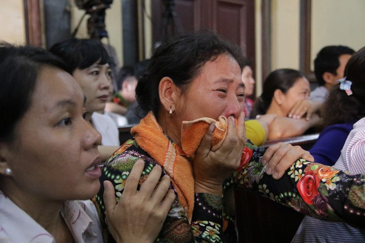 Người nhà bị hại cố chèn chiếc khắn che miệng để không khóc thành tiếng.