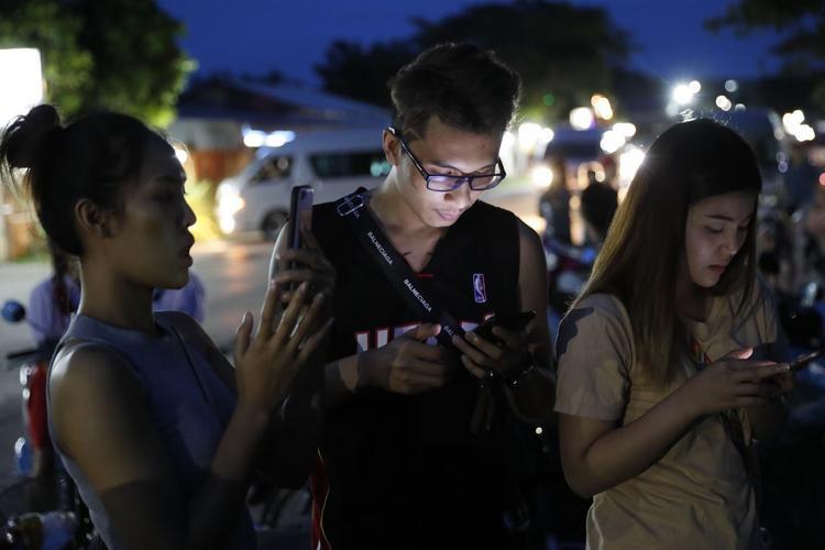 Mọi người đứng chờ bên ngoài căn cứ không quân, liên tục tuy cập internet để cập nhật được tình hình cứu hộ. Ảnh: Vincent Thian/AP