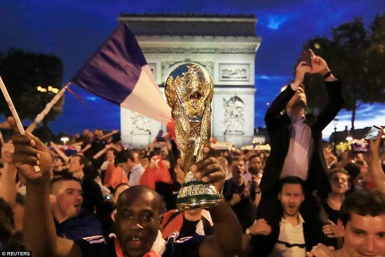 Người đàn ông này còn cầm trên tay chiếc cúp vô địch với hy vọng đội tuyển Pháp có thể trở thành nhà vô địch bóng đá thế giới. Ảnh: Reuters