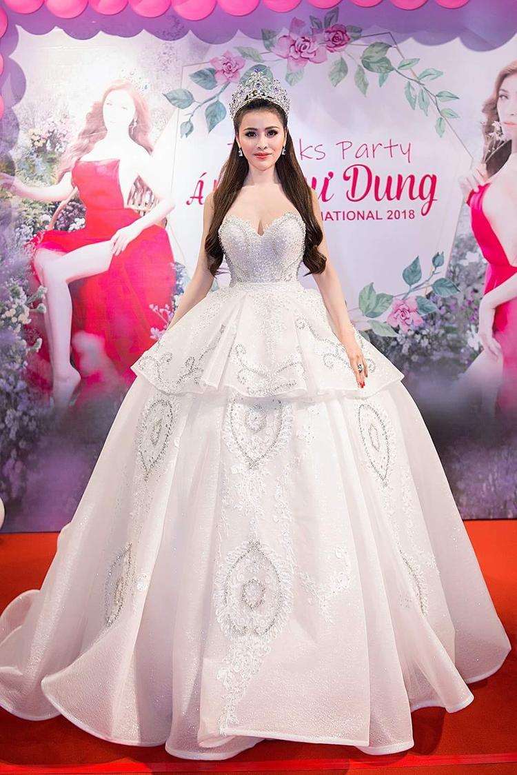 Với chiếc váy này, người đẹp chọn kiểu tóc buộc cao gọn gàng và làm điểm nhấn phần đuôi tóc cùng với chiếc vương miện danh giá tại Miss Eco International 2018.