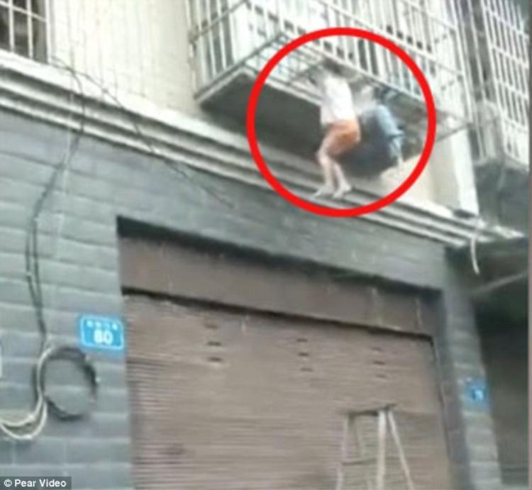 Hai đứa trẻ treo lơ lửng ở ban công tầng 1.