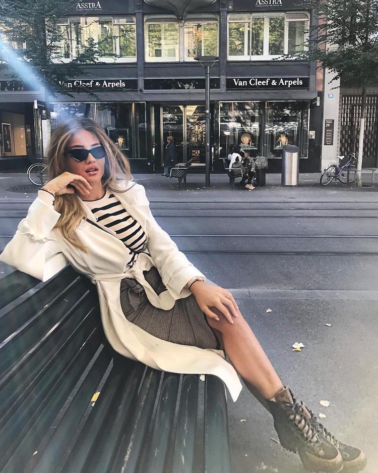 Bộ trang phục dạo phố đơn giản với áo phông kẻ cắm thùng cùng chân váy bút chì bỗng trở nên thời thượng khi Izabel khoác thêm 1 chiếc cardigan trắng dáng dài phía bên ngoài và nhấn nhá cùng kính mát mắt mèo, giày hầm hố.