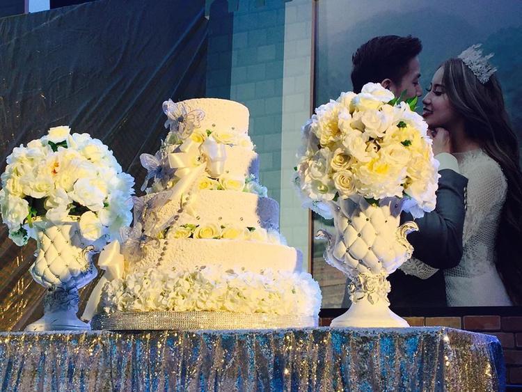 Bánh cưới màu trắng được trang trí hoa tươi.